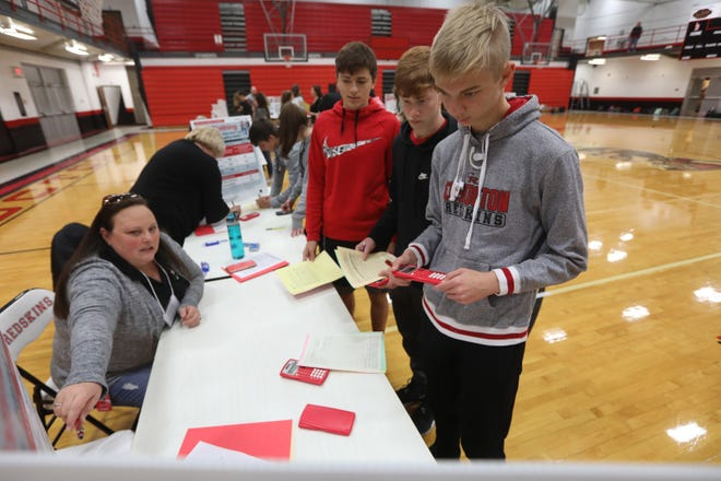 Coshocton High School students Alec Laaper, right, Zach Jennings and Jacob Lonsberry listen as Amber Lovett explains their options for communications during the Real Life Real Money program at Coshocton High School. The program helps students learn budgeting and gives them a view of the real life expenses.