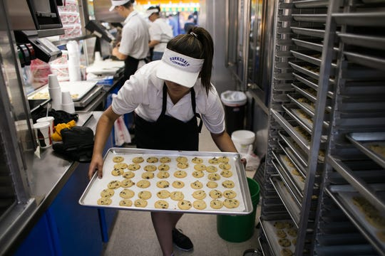 Jaxin Teran, 18 of Des Moines transfers chocolate chip cookies onto racks inside the Barksdale Cookies stand during the 2015 Iowa State Fair.
