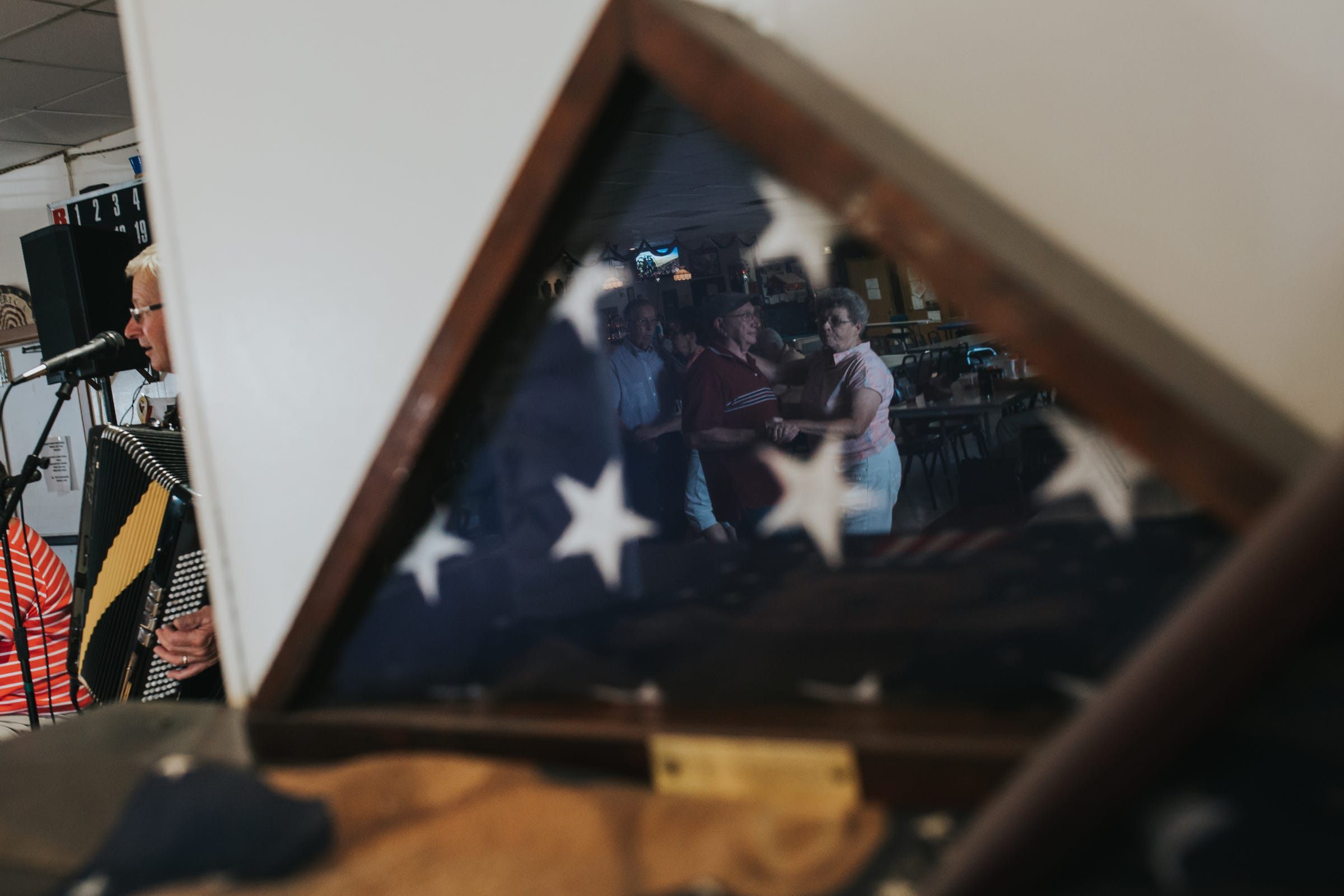 Dancers are reflected in a flag's display case during a weekly polka dance held at VFW Post 4573 in Ishpeming in Michigan's Upper Peninsula on Saturday, Aug. 19, 2017.