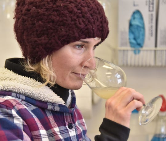 Winemaker Kasey Wierzba sniffs a sample of wine in the lab at Shady Lane Cellars, south of Suttons Bay.