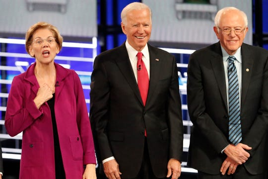 Democratic presidential candidates Sen. Elizabeth Warren, D-Mass., left, gestures as former Vice President Joe Biden, center, and Sen. Bernie Sanders, I-Vt., watch before a Democratic presidential primary debate, Wednesday, Nov. 20, 2019, in Atlanta.