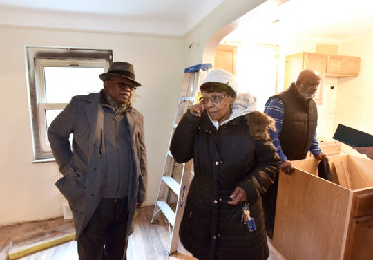 Means Group consultant Edward McNeil, left, of West Bloomfield Township, reaches for a handkerchief as Doris McCarver wipes joyful tears from her eyes in the dining room of her new home that is under renovation. At right, her pastor, Calvin Landrew of Real Spirit Tabernacle in Detroit, talks in the kitchen.