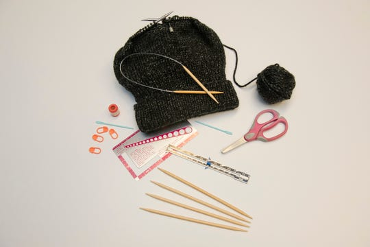 This photo shows all the materials and tools needed to hand-knit hats for the homeless.