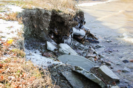 In a Nov. 8, 2019 photo, a grindstone lies broken on the eroded shoreline in Grindstone City, Mich. Like many shoreline communities, the high water and strong currents have wreaked havoc on the community.
