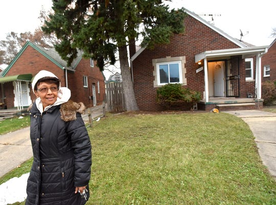 Doris McCarver walks across the yard in front of her new Highland Park home, being renovated by developer Eric Means. Means bought her old house as part of a development plan and renovated a different house for her.