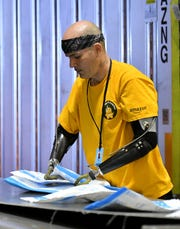 Kevin Blackburn, 42, of Trenton sorts packages at the Amazon Brownstown Sortation Center in Brownstown on Nov. 19.  Blackburn started at Amazon in July and was recently named associate of the month.