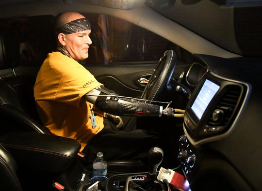 Kevin Blackburn, 42, gets ready to head to work at the Amazon Brownstown Sortation Center from his home in Trenton.  Prosthetics on both arms make it possible for Blackburn to have the freedom of mobility.