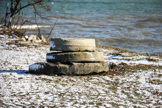 In a photo from Nov. 8, 2019, grindstones, recently unearthed, are displayed on the shoreline in Grindstone City, Mich. Like many shoreline communities, the high water and strong currents have wreaked havoc on the community.