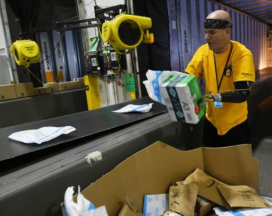 Kevin Blackburn, 42, of Trenton sorts packages at the Amazon Brownstown Sortation Center in Brownstown, Mich. on Nov. 19, 2019.  Blackburn started at Amazon in July 2019 and was recently named associate of the month.