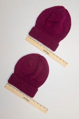 This photo shows that the top hat, hand-knitted using metal knitting needles, is a quarter inch wider than the bottom hat, which was hand-knitted using wooden knitting needles and the same yarn. Because the metal needles are slippery, the weave is not as tight as that achieved using the wooden needles.