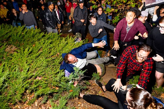 """A man leaving a speech by conservative commentator Ann Coulter falls to the ground after being pushed by protesters at the University of California, Berkeley, Wednesday, Nov. 20, 2019, in Berkeley, Calif. Hundreds of demonstrators gathered as Coulter delivered a talk titled """"Adios, America!"""""""