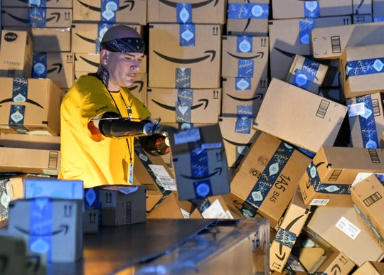 "Kevin Blackburn, 42, of Trenton sorts packages at the Amazon Brownstown Sortation Center in Brownstown.  ""Since I started working, my attitude about everything is different,"" he said."