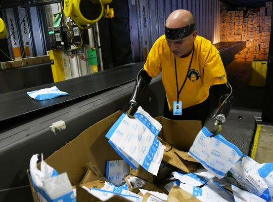 Kevin Blackburn, 42, of Trenton sorts packages at the Amazon Brownstown Sortation Center in Brownstown on Nov. 19.  Blackburn started at Amazon in July 2019 and was recently named associate of the month.