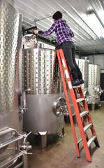 Shady Lane Cellars winemaker Kasey Wierzba checks fermenting wine from a storage tank at the Leelanau County winery.