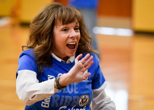 Loge Elementary Principal Lynne Pierce waves to the student body during a surprise assembly to celebrate the school winning a Blue Ribbon School Award Thursday, November 21, 2019.