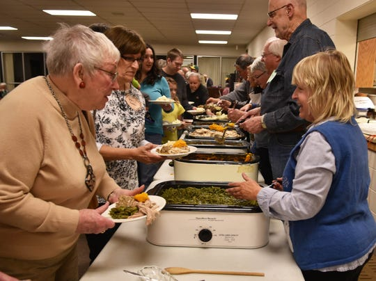 Leonette Tackenberg of Sturgeon Bay, left, talks to volunteers in the serving line during a previous Community Thanksgiving Dinner at Sturgeon Bay United Methodist Church. The church serves about 150 people each year at the church, with a similar number of take-out and home delivery meals.