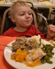 Bradley Stanley digs into his plate of turkey with all the trimmings during a previous Community Thanksgiving Dinner at Sturgeon Bay United Methodist Church. The church serves about 150 people each year at the church, with a similar number of take-out and home delivery meals.