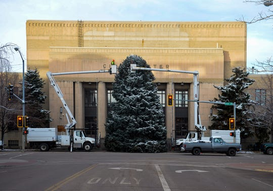 City crews place lights on the Christmas tree at the Civic Center.