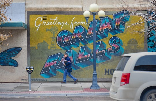 A U.S. Post Office mail carrier makes his rounds in downtown Great Falls on Wednesday afternoon, November 20, 2019.