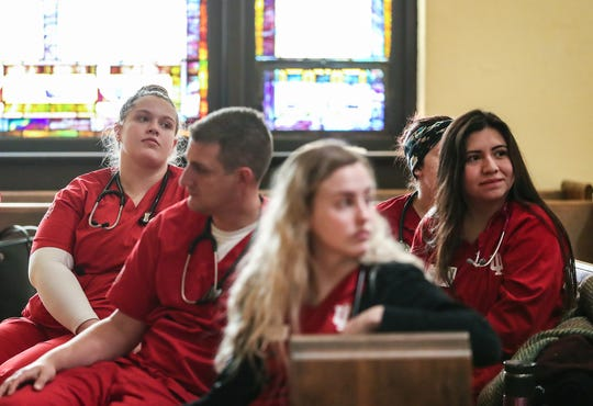 Nursing students listen to a debriefing in the chapel of Neighborhood Fellowship Church on the near east side of Indianapolis on Saturday, Nov. 16, 2019, at the start of a weekly clinic that offers free health care services to the community. If enough money is raised, the clinic will expand its operation to a large vacant commercial space across the street.