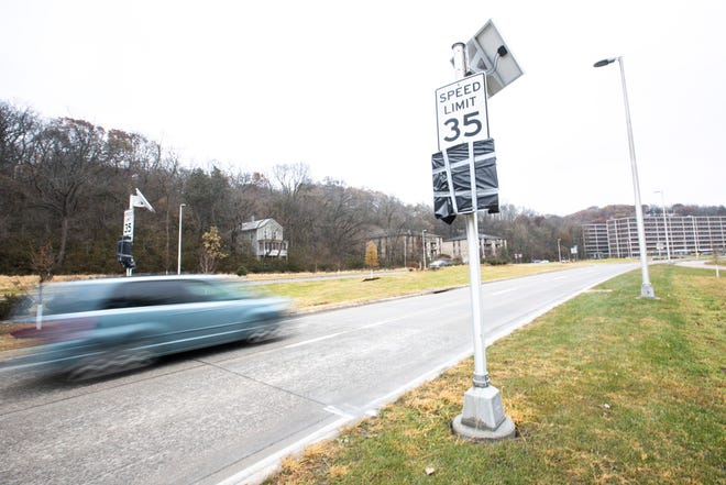 Plastic trash bags cover speed indicators as cars drive past a newly posted 35 mile per hour speed limit sign, Tuesday, Nov. 19, 2019, along Dubuque Street in Iowa City, Iowa.