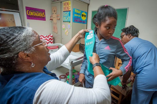 Before the Wednesday, Nov. 20, 2019, meeting at Pearl Street A.M.E. Church in Jackson, Girl Scout leader Cassandra Stovall, from left, helps Junior Scout Payton Jackson, 9, of Terry, with her sash as her grandmother Venessia Johnson collects her fall fundraising items that need to be distributed.