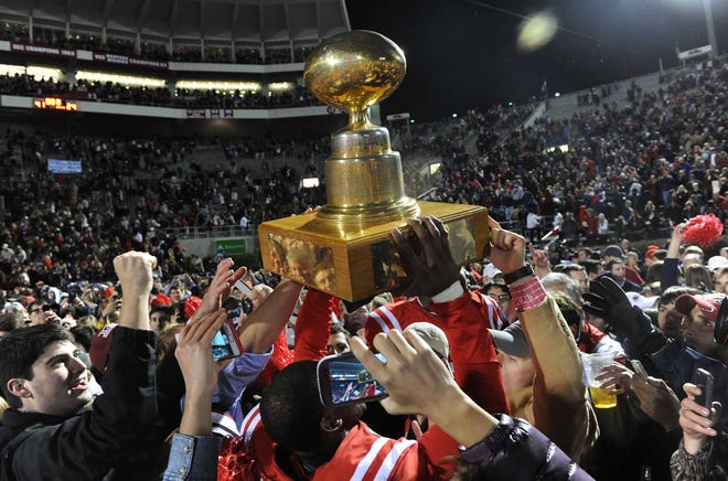 Ole Miss fans and players celebrate with the Egg Bowl trophy after beating MSU 41-24 in Oxford.