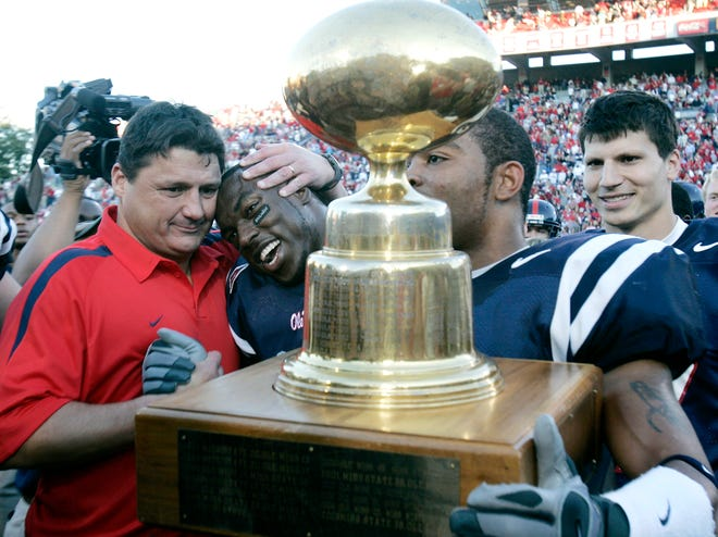 Mississippi coach Ed Orgeron, left, hugs linebacker Patrick Willis (49) as other players carry the Egg Bowl trophy that goes to the winner of the annual football game between Ole Miss and Mississippi State, in Oxford, Miss., Nov. 25, 2006.