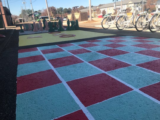 The new pop-up park on Highland Avenue includes a checkerboard for gaming purposes.