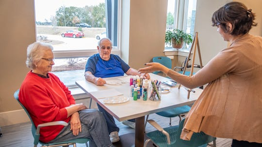 Linda and Charles Becnell sit at an arts and craft table at Avanti Senior Living in Lafayette as staff member Catherine Roy talks to them.