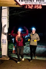 Brighton woman Loretta Tobolske-Horn (left), 48, crosses the finish line of the Tunnel Hill 100-mile race on Nov. 9, 2019 in Vienna, Ill. She spent months training for the race with world record holder Zach Bitter. Accompanying her was her daughter Maddelynn (right).