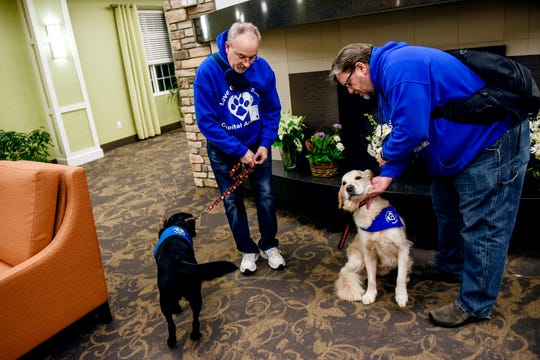Scott Grammer and his golden retriever Fletcher, right, and  Scott Yeske with his black lab Tasha prepare to meet with residents for dog therapy at the Regency Lansing West senior living facility on Wednesday, Nov. 20, 2019, in Delta Charter Township. Grammer and other volunteers and their dogs from the local chapter of Love on a Leash meet with residents once a week.