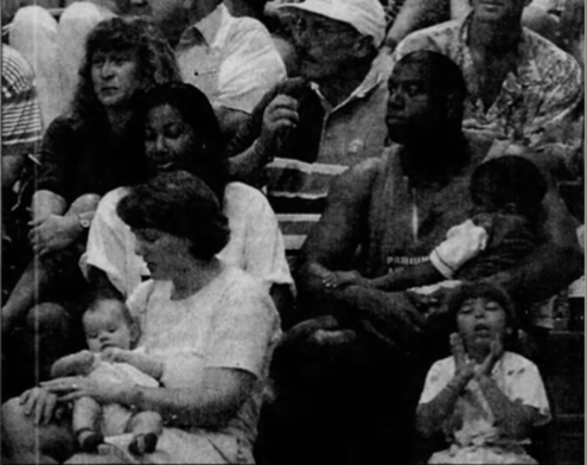 Magic Johnson watches Michigan State lose 92-70 to North Carolina on Nov. 21, 1995 at the Maui Invitational, while holding his son, Earvin Jr. His wife Cookie is to his right.
