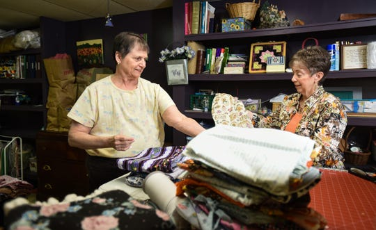 Linda Mahan, left, of Holt talks about the 2,000 of handcrafted dresses she makes at home, and then sends to girls in impoverished areas.  She is pictured Wednesday, Nov. 20, 2019, in her sewing room with friend Connie Swix of Lansing.