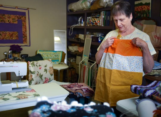 Linda Mahan of Holt shows the types of dresses she makes to send overseas, Wednesday, Nov. 20, 2019.  Over the past five years, Mahan has sewn 2,000 handcrafted dresses that she gives to girls in impoverished communities.