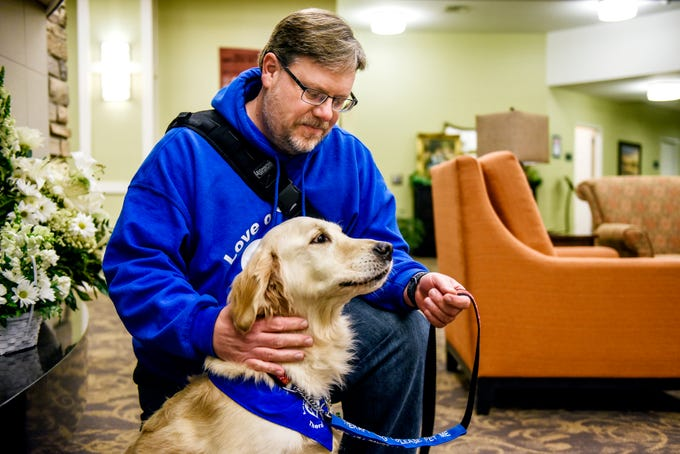 Scott Grammer pets his golden retriever Fletcher at the Regency Lansing West senior living facility on Wednesday, Nov. 20, 2019, in Delta Charter Township. Grammer and other volunteers from the local chapter of Love on a Leash meet with residents once a week for dog therapy.