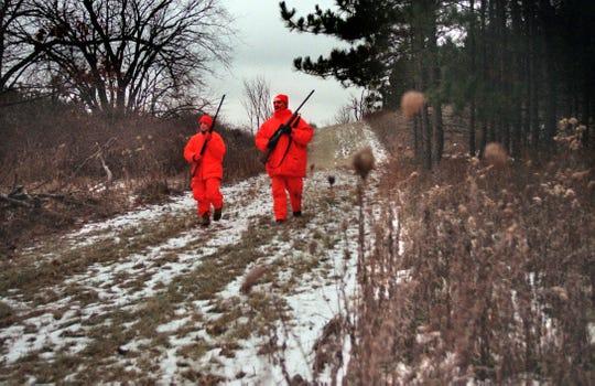 Deer hunters walk on a trail near Dundee, Wis.