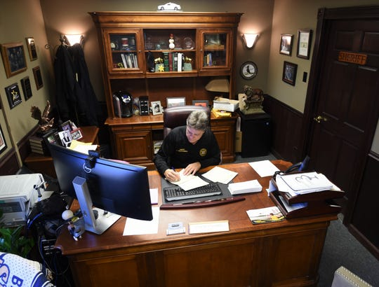 Baxter County Sheriff John Montgomery signs restitution checks Tuesday afternoon in his office. The Sheriff's Office has returned more than $3 million in restitution since Montgomery took office in January 2005.