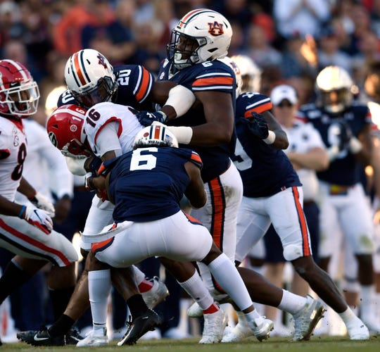 Auburn's Christian Tutt (6), Derrick Brown (5) and Jeremiah Dinson (20) tackle Georgia's Demetris Robertson (16) on Nov. 16, 2019 in Auburn, Ala.
