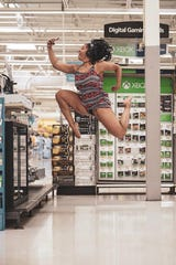 Bella Kash leaps high, like one of the video game characters in Walmart's electronics section.