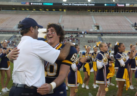 Naples head coach Bill Kramer gives Kurt Hussey a hug Friday after the 2007 FHSAA 3A Football Finals at the Citrus Bowl in Orlando. Naples won the game 17-10.