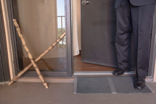A sugarcane cross leans outside  Mamberto Real's apartment as a symbol for protection on Thursday, Nov. 21, 2019, at Bonair Towers senior apartments in Fort Myers.  He is facing eviction by the Fort Myers Housing Authority, which found that his behavior is disruptive. Real says the eviction stems from his practice of Santeria.