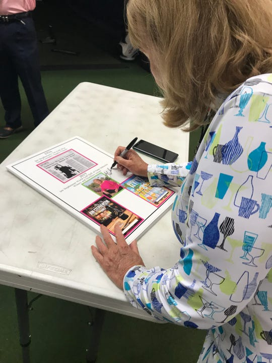 World Golf Hall of Famer Jan Stephenson signs a poster while selling her wine at PGA Tour Superstore on Wednesday, Nov. 20, 2019 in Naples.