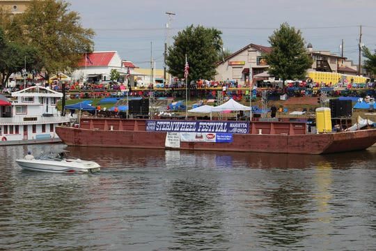 People line the banks of the Ohio River, waiting for the official announcements from the Sternwheel Festival barge.