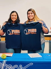 Loving's Andrica Gomez, left, and Lorisa Martinez display their Pima CC shirts after signing letters of intent to play softball next season.