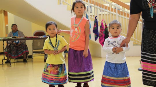 Mila Phillips, left, Emily Phillips, center, and Gabrielle Atene, right, participate in the Native Skirts Fashion Demo at Northern Navajo Medical Center in Shiprock on Nov. 20, 2019.