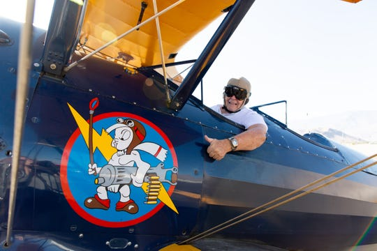 Bill Griffin gives an enthusiastic thumbs-up from the cockpit of his biplane.