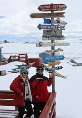 Graduate student Leila Harris and UWF professor Wade Jeffrey pose with the Pensacola arrow on a pole with the other direction signs at the Palmer Station.