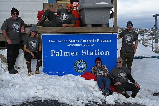 The group poses in front of the Palmer Station sign.