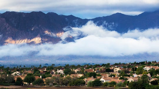 Rain clouds hover over the mountains looking west on Chandler Boulevard near South Third Street in Phoenix on Nov. 21, 2019.
